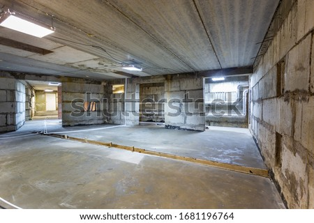 Concrete construction of basement of large building. Ground floor Inside the modern construction site in a mix of fluorescent and natural lights. Contemporary structure under construction with concret stock photo
