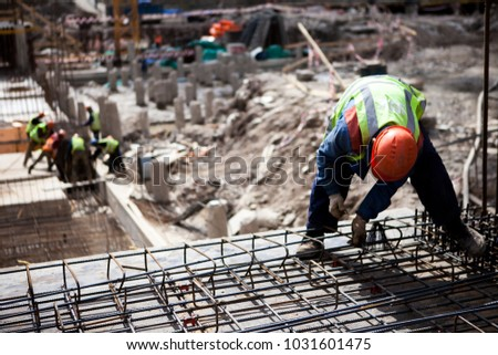 Concrete construction worker working with steel rebar at construction site