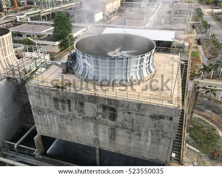 Concrete cooling tower and cooling fan blowing steam on the air #523550035