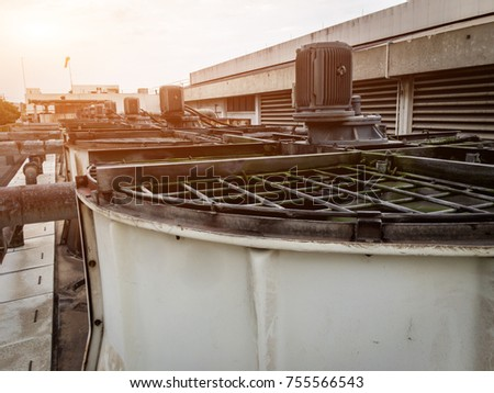 Concrete cooling tower and cooling fan blowing steam on the air In the factory.cooling tower and outdoor. #755566543