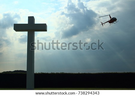 Concrete cross as memorial at Schaffen airfield, with helicopter in backlight