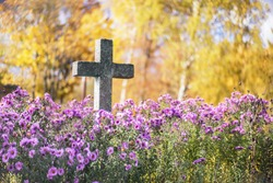 Concrete cross in cemetery in autumn