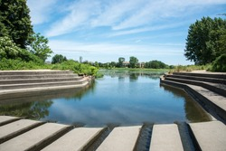 Concrete dam and steps with lush landscape and peaceful water view at the community park nature reserve in Eola, Illinois