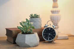Concrete decorative plant pot and metal clock on the work table. Decorative items on the office table. Decorative flower pot, book and clock