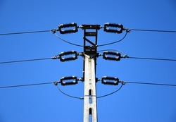 Concrete electrical pole in low angle view. high voltage electrical wires. brown ceramic isolators. blue sky background. electrical supply and distribution.