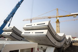 Concrete elements for a subway tunnel. Big and heavy parts for the underground cylindrical tunnel construction. Cranes.