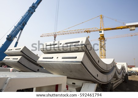 Concrete elements for a subway tunnel. Big and heavy parts for the underground cylindrical tunnel construction. Cranes. stock photo