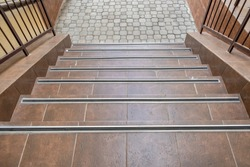 Concrete entrance stairs covered with ceramic tiles with metal railings outdoors.