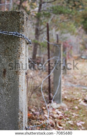 Concrete fence post and barbed wire