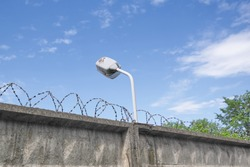 Concrete Fence with Barbed Wire and Surveillance Camera