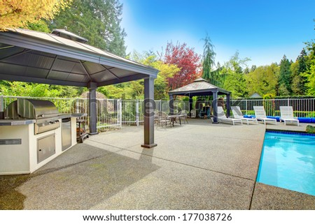 Concrete floor patio area with barbeque, table set, sun chairs and swimming pool