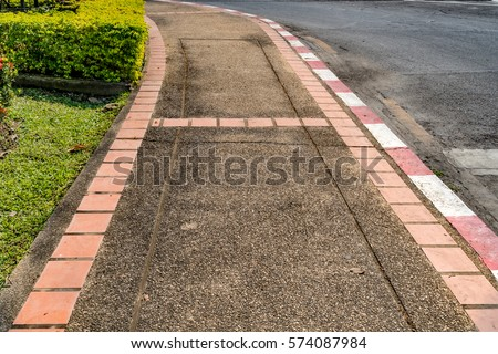 Concrete gravel sidewalk with red and white curb