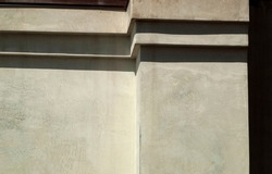 Concrete gray-beige wall of the house with straight ledges of the type of steps in the upper part. Texture surface is visible. Minimalism and geometric. Bright sunlight, clear shadows. Horizontal.
