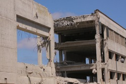 Concrete industrial building destroyed - building destruction with blue sky and clouds background