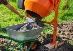 concrete is loaded into a cart from a 200 liter orange electric concrete mixer, photo taken on a sunny summer day outdoors