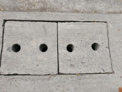 Concrete manhole cover with vent hole.