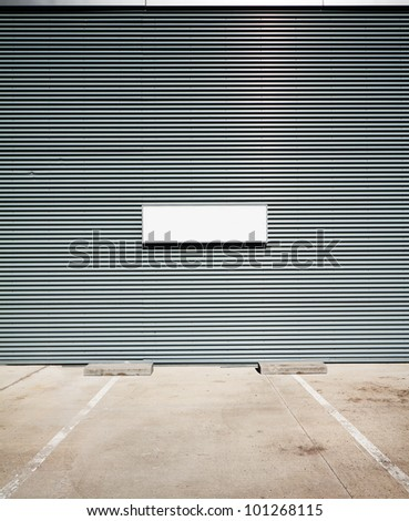Concrete parking floor and tin wall with blank info board.