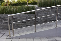 Concrete path with stone tile floor and steel banisters in front of the house or buildings