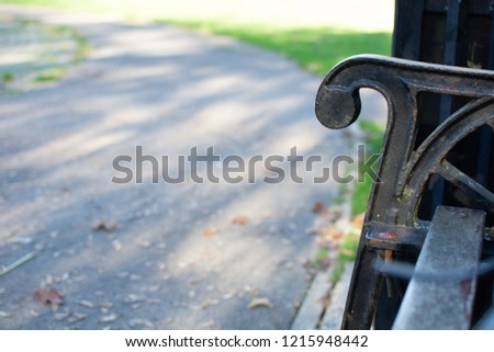 Concrete pavement forming a path up to a wooden and metal bench in a park leading to grass lawn. Moss can be seen growing on the benches arm #1215948442