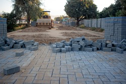 Concrete pavers being used to replace a dirt road