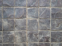 Concrete paving stone texture. Covering the sidewalk. Square tiles. Sand and dirt in the joints between tiles.