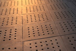 Concrete paving tiles with regular holes under tungsten light.