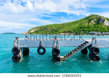 Concrete piers, staircase with rubber bumper in the sea mountain is background #1186065055