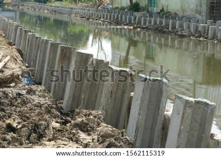 Concrete piles are put along canal.