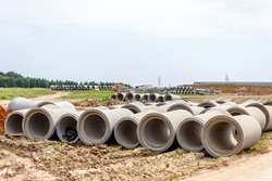 Concrete pipes for the construction of objects lie on the ground. The concept of construction works.