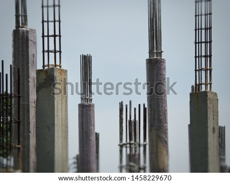 Concrete poles and steel structure in construction, are important part for building structures, with blue sky background.