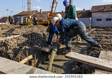 Concrete pouring. Construction workers are pouring concrete in building foundation, directing the pump tube on right direction.