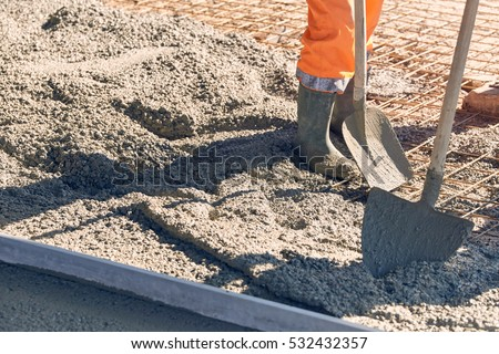 Concrete pouring during commercial concreting floors of building\ Worker with gum boots spreading ready mix concrete