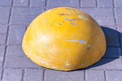 Concrete protective pavement hemisphere close-up, scratched yellow pavement hemisphere