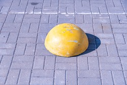 Concrete protective pavement hemisphere, scratched yellow pavement hemisphere