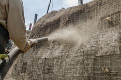 Concrete pumping hose used to cover with cement a construction wall  Cement applied with high pressure to create masonry walls