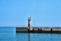 concrete sea berth or pier with signal beacon and with car tires for mooring boats and yachts and horizon of sea and sky