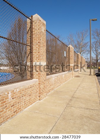 Concrete Sidewalk By Brick Columns And Chain Link Fence