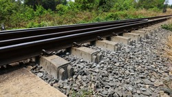 Concrete sleepers for railway tracks. Steel railway rails are fixed to concrete sleepers on stone beds, closed on sunny days. Selective focus
