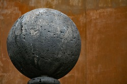 concrete sphere sculpture in front of wall
