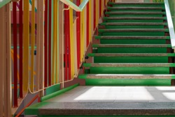 concrete staircase with green steps and multi-colored railing
