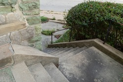 Concrete stairs descending around an outside corner of a building made from crumbling green limestone, black handrails on steep descent, horizontal aspect