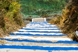 Concrete stairs down to ocean. Steps painted in colors of Greek flag, go down to sea waves. Varkotopos beach in sea bay of resort village Bali. Sheer cliff washed by waves. Crete, Greece