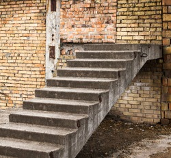 Concrete stairs in the unfinished brick building. Construction site.