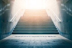 Concrete stairs leading up towards light. Concept of hope and bright future