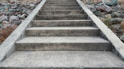 Concrete stairs with rocks beside.