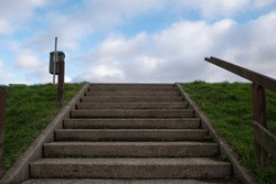 Concrete stairs with wooden handrail blue sky and white clouds