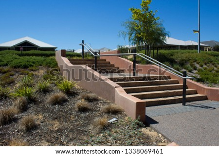 Concrete steps leading up to the street  from the green parklands  at Dallyellup beach near Bunbury western Australia  offers a calm relaxing scene on a sunny bright  morning in summer. #1338069461