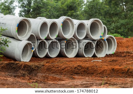 Concrete storm water drain pipes lay stacked on raw earth awaiting installation into civil engineering road project improvements