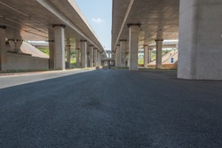 Concrete structure and asphalt road space under the overpass in the city