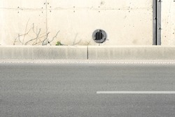 Concrete structure detail and a part of a highway. Concrete wall texture with a round ventilation hole.